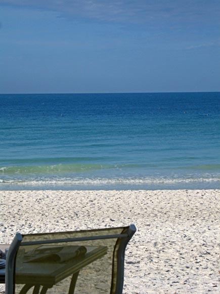 sling chair on white sand beach, anna maria island, florida
