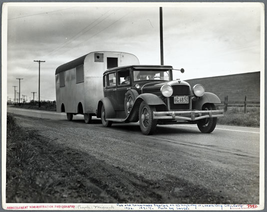 """Car and homemade trailer on U.S. 101 near King City, California. Man and wife middle-aged, from Wisconsin. """"Old Man Depression sent us out on the road ... You don't know anything about how many people are living in trailers till you 'hit' Florida, 1936, by Dorothea Lange (1895-1965). Photograph. The Miriam and Ira D. Wallach Division of Art, Prints and Photographs: Photography Collection, The New York Public Library. The New York Public Library Digital Collections."""